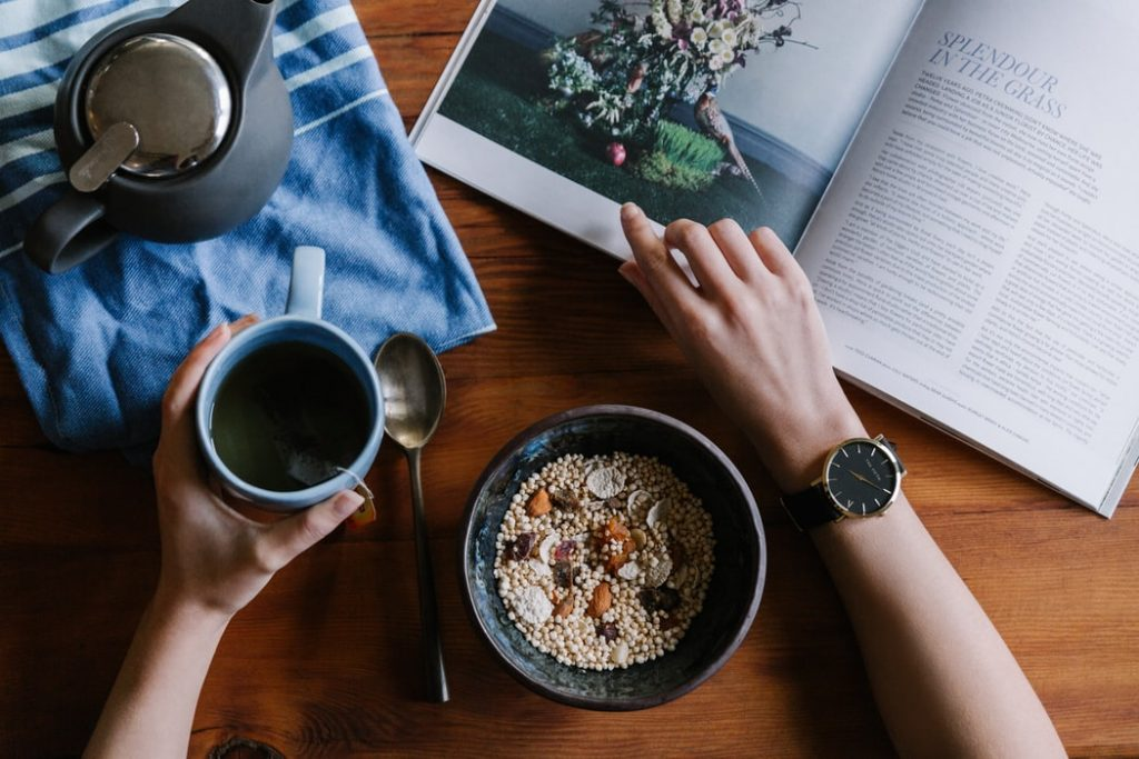 A person eating breakfast and reading a magazine