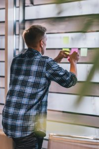 man setting priorities by using post-it notes on a window