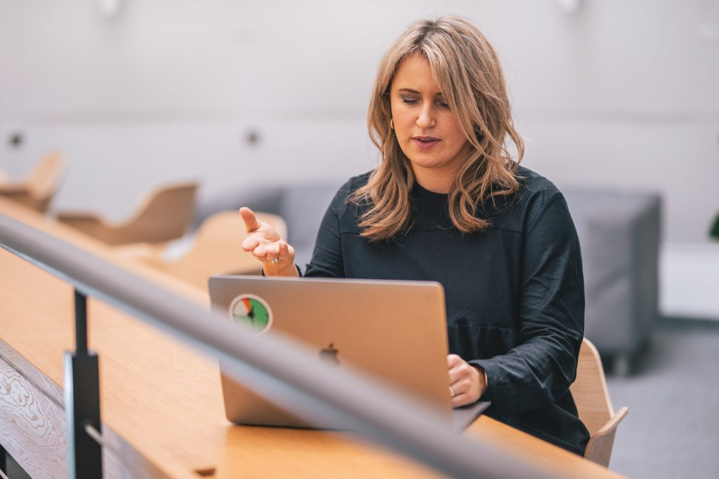 Woman pointing at computer during remote meeting