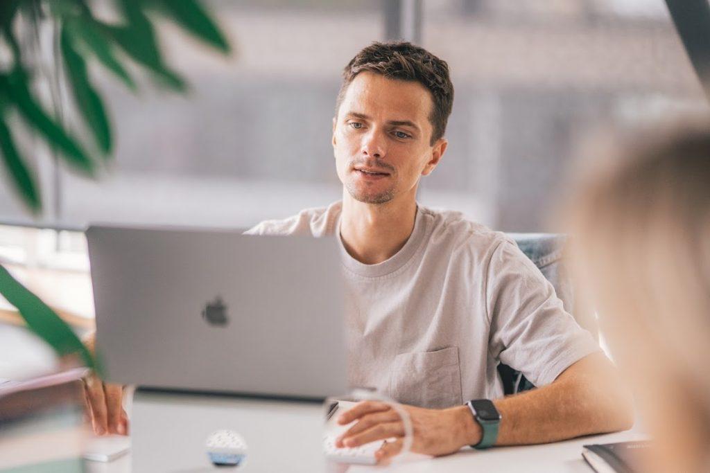 Man hosting a hybrid meeting on his laptop