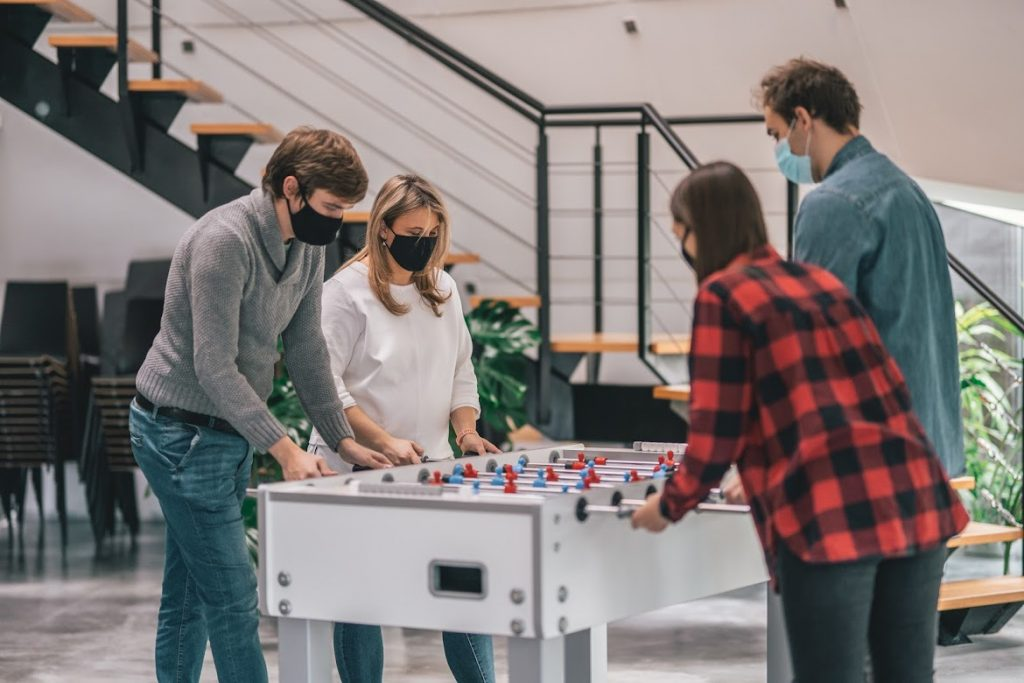 Team playing table football in office